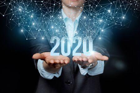 Das neue Konzept 2020 im Geschäft. Geschäftsfrau, die 2020 auf schwarzem Hintergrund zeigt.
