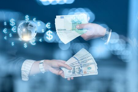 The concept of currency exchange. Hand with Euro and dollars on blurred background. Фото со стока
