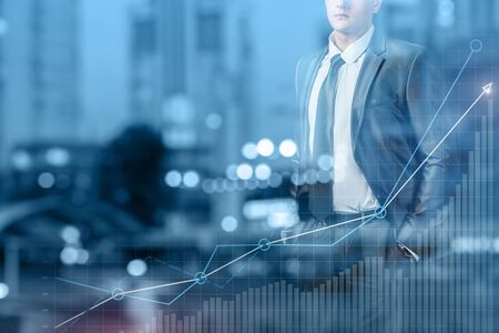 The concept of successful and profitable business. Businessman standing on background of the city and chart financial growth.
