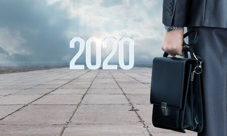 Concept the way to new 2020. Businessman standing on the road with a bag in front of the numbers 2020.