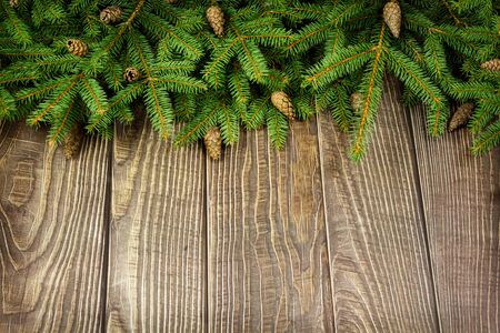 Sprigs of Christmas tree and cones on wooden background.
