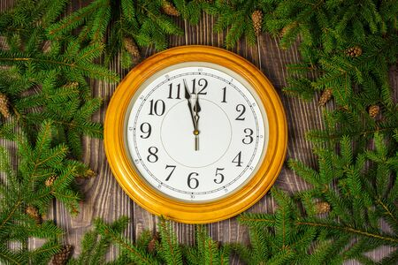 The twigs of Christmas tree wall clock on wooden background.