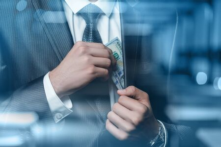 Businessman pulls out a bundle of dollars on a blurred background. Stok Fotoğraf