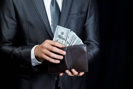 Businessman pulls out a banknote of dollars out of wallet on a dark background. Stok Fotoğraf