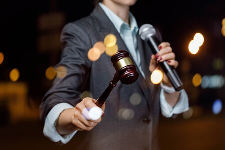 The auctioneer conducts the auction with a microphone on blurred background. Stok Fotoğraf
