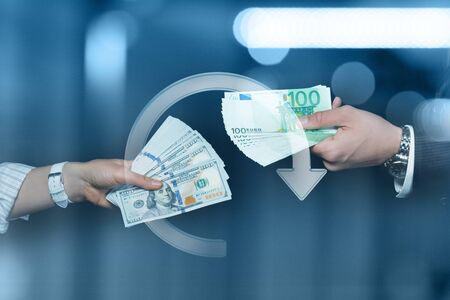 The concept of exchange of dollars and euros. Businessmen with banknotes of dollars and euros on a dark background