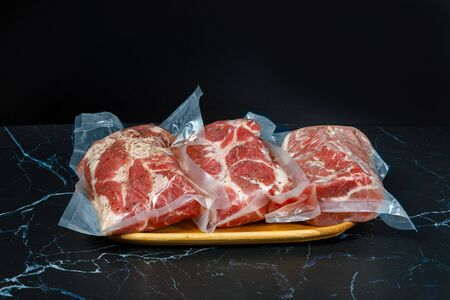 The meat is packed in a vacuum on a wooden tray.