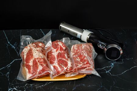 Meat and Sous Vide Cooker Immersion Circulator on a dark background. 스톡 콘텐츠