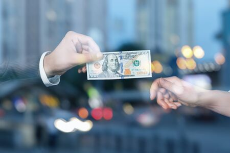 Hand of businessman holds out a hundred dollars to a businesswoman in the blurred background. Stok Fotoğraf