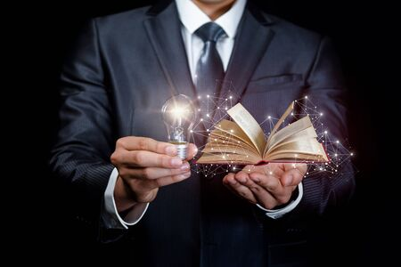 The concept of knowledge source of ideas in business. Businessman showing a burning lamp and tutorial.