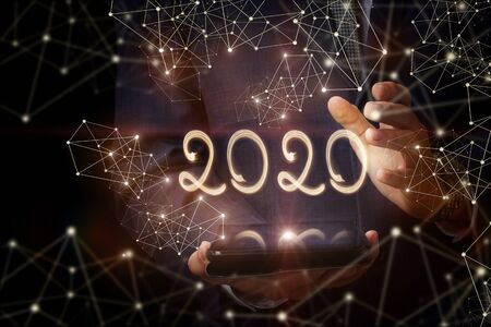 The concept new 2020 year . The numbers 2020 shows a businessman using a mobile device on a dark background. Banco de Imagens