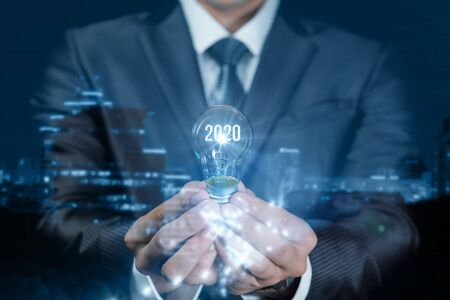 The concept of a new idea in 2020. Businessman holding a light bulb with glowing numerals 2020 and town in the background.