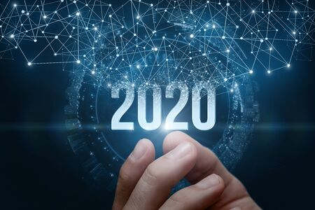 The hand shows the numbers 2020 on a dark background. The concept new 2020 year .