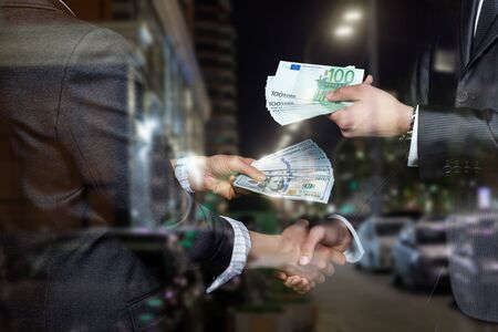 The concept of currency exchange. Businessmen give each other paper dollars and euros.