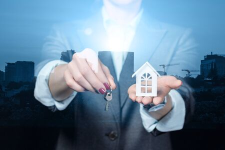 The concept of buying or renting real estate . Businesswoman showing model house and keys.