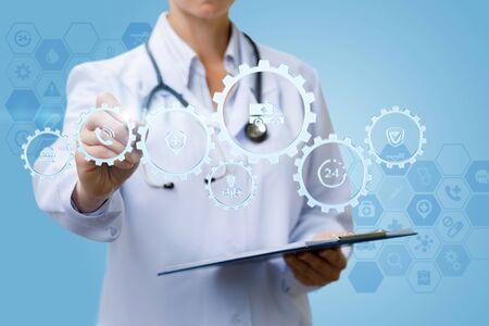 Der Arzt arbeitet mit dem Mechanismus des Gesundheitswesens auf blauem Hintergrund.