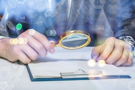 Ein Anwalt oder ein Geschäftsmann, der ein Dokument mit einer Lupe untersucht. Standard-Bild