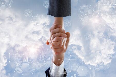 The concept of business cooperation or contract. Handshake of businessmen on background of the sky.