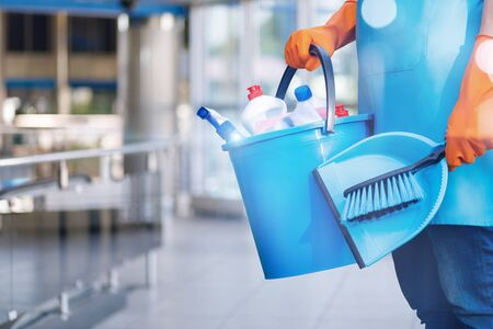 The concept of clening service. The cleaning lady stands with a bucket and a shovel on blurred background.