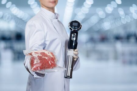 Sous vide cooking. Shows cook sous vide immersion circulator cooker and the meat in the package.