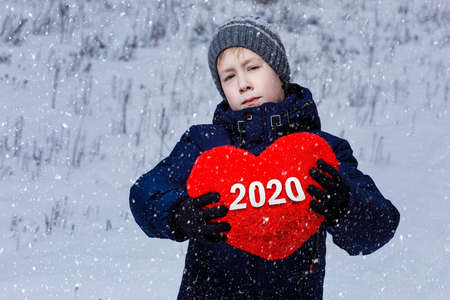 The boy shows a heart with the numbers 2020 year on a snowy background.