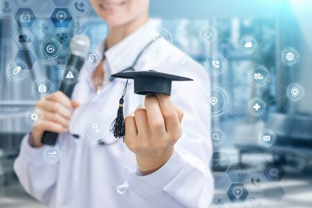 Concept study and presentation of medicine. Doctor with microphone in hand shows academic hat on blurred background.