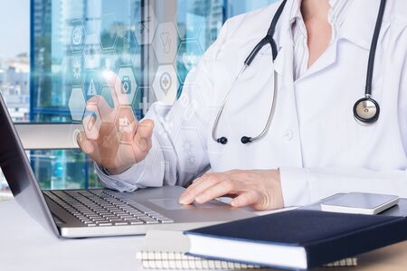 The concept of virtual health care. The doctor works on the virtual screen. Banco de Imagens
