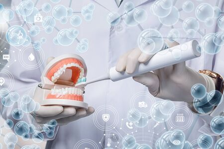 The concept of dental hygiene. Doctor shows how to brush your teeth. Imagens