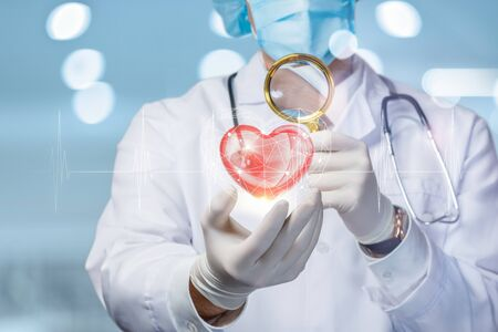 The concept of diagnosis and study of the heart. The doctor looks through a magnifying glass on the heart.