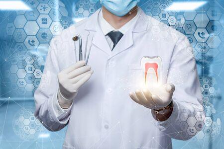 El concepto de diagnóstico y tratamiento de los dientes. El doctor muestra un modelo de diente en una pantalla virtual. Foto de archivo