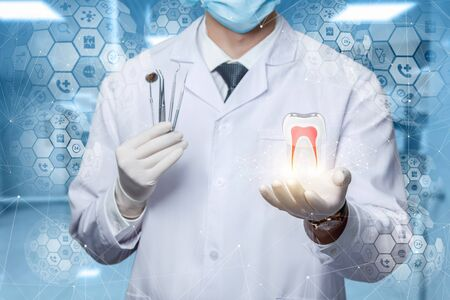 The concept of diagnosis and treatment of the teeth. Doctor shows a tooth model on a virtual screen. Stock Photo