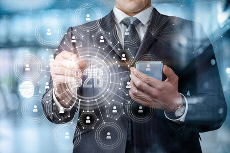 The concept of information and economic interaction between business to business. The businessman draws the B2B network connections.