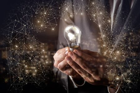 The concept of global ideas.Businessman holds a burning light bulb in the global network.