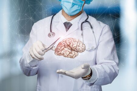 The concept of treating the brain of a patient. The doctor shows the brain. Stock Photo