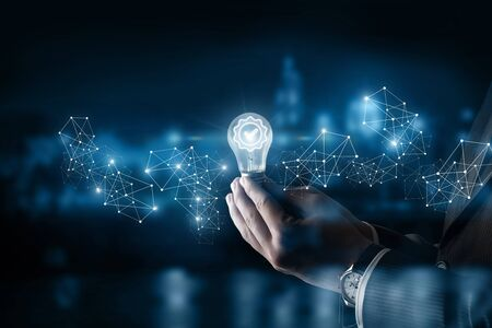 The concept of a quality idea. Hand shows a burning light bulb .
