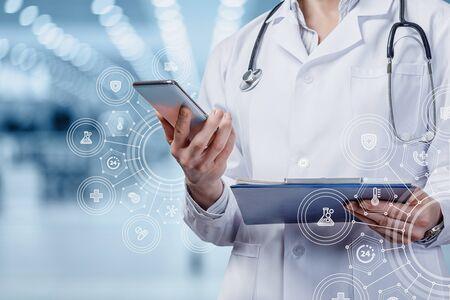 医療サービスの提供において、モバイル機器を支援するという概念。医師はぼやけた背景に携帯電話で働いています。