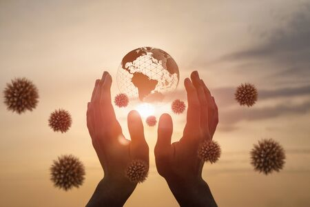 Concepts of protecting the world from a virus.Hands support a planet surrounded by a virus.