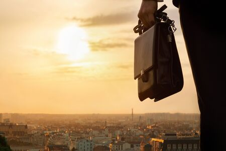 A Businessman with a bag stands against the backdrop of the city panorama and sunny sunset.