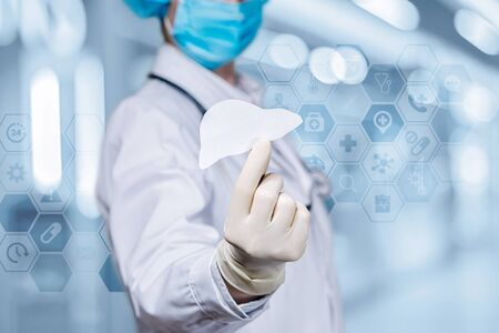 The doctor holds a liver in hand on a blurred background. Stock fotó