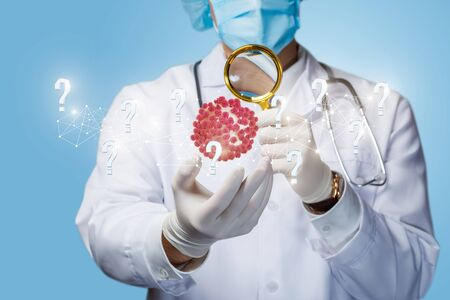 The concept of research and study of the virus. The doctor looks through a magnifying glass at a virus on a blue background.