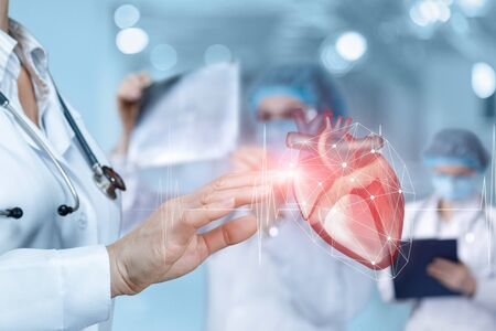 Doctor clicks on a heart with a pulse on a blurred background.