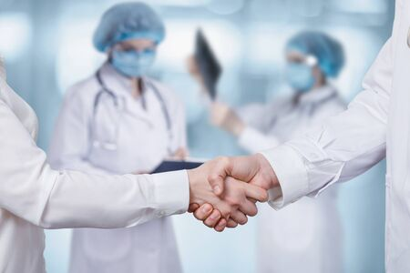 Handshake of doctors on a blurred background.