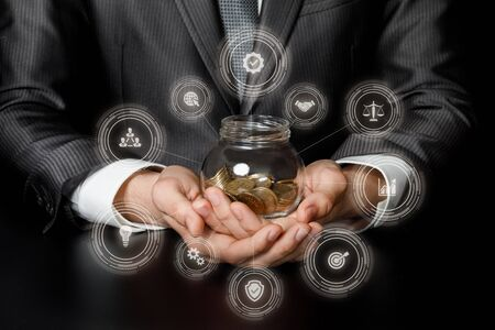 The concept of saving in business. Businessman with a jar of coins in his hands against a dark background.