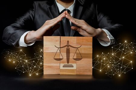 The concept of protection of justice.Businessman protects the scales with hand gestures. Zdjęcie Seryjne