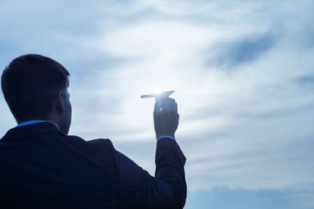 Business man holds an airplane in the sunlight.