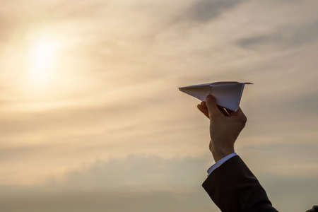 Hand launches an airplane in the direction of the sun on a blurred background. Archivio Fotografico