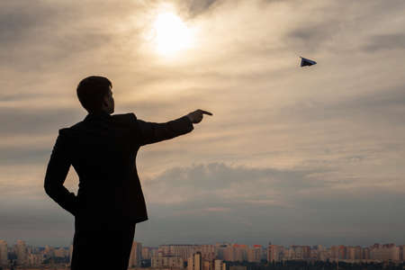 Businessman launches an airplane against the background of the city.