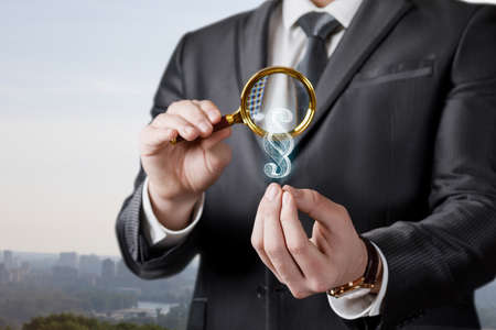 A lawyer looks through a magnifying glass at a paragraph on a blurred background. 版權商用圖片