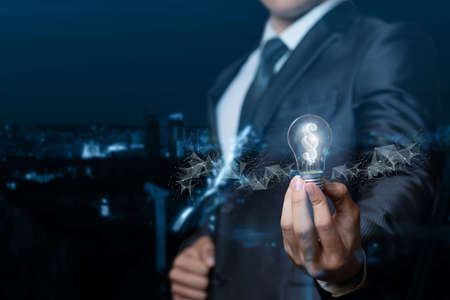 A lawyer or businessman showing light bulb burning inside the paragraph on blurred background. 版權商用圖片