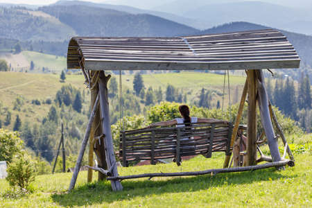A woman sits on a swing looking at the highlands. Stockfoto